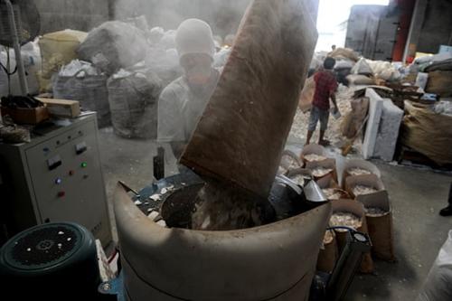 Công nhân trút bỏ xốp vụnvào máy nghiền trong cơ sở tái chế ở thành phố Valenzuela, phía bắc Manila. Ảnh: AFP.