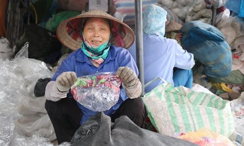 Bà Nguyễn Thị Hồng Thắm cầm một vỏ nhựa bọc kẹo xuất xứ từ Mỹ. Ảnh: Guardian.