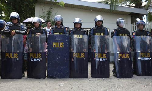 Cảnh sát vũ trang Philippines bên ngoài căn nhà diễn ra cuộc gặp giữa Bộ trưởng Nông nghiệp và 22 ngư dân hôm 19/6. Ảnh: Rappler.