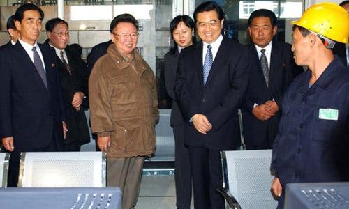Chủ tịch Trung Quốc Hồ Cẩm Đào (phải) cùng lãnh đạo Triều Tiên Kim Jong-il thăm một nhà  máy sản xuất gương ở ngoại ô Bình Nhưỡng hồi tháng 10/2005. Ảnh: AP.