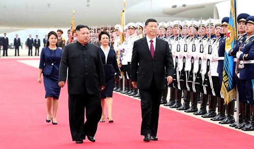 Ông Tập(phải) vàKim Jong-un duyệt đội danh dự ở sân bayhôm 20/6. Ảnh: CCTV.