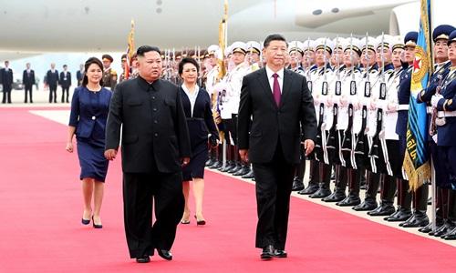 Chủ tịch Trung Quốc Tập Cận Bình (phải) và lãnh đạo Triều Tiên Kim Jong-un duyệt đội danh dự tại sân bay ở Bình Nhưỡng hôm 20/6. Ảnh: CCTV.