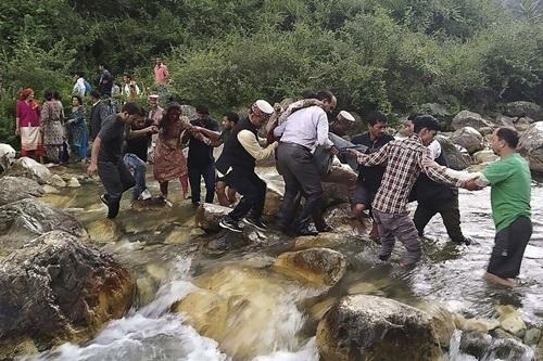 Người dân đưa thi thể và người bị thương rời hiện trường tai nạn ở huyện Kullu chiều 20/6. Ảnh: AFP.