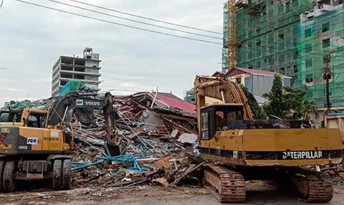 Máy xúc dọn dẹp đống đổ nát, nơi hàng chục người đang mắc kẹt tại thành phố Sihanoukville hôm nay. Ảnh: AFP.