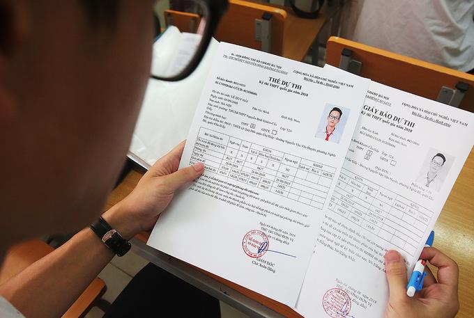 Thí sinh thi THPT quốc gia 2018 đối chiếu thông tin ở giấy báo dự thi và thẻ dự thi. Ảnh: Ngọc Thành