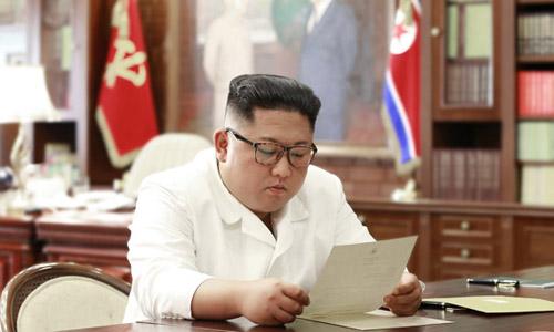 Lãnh đạo Triều Tiên Kim Jong-un đọc thư từ Tổng thống Mỹ Donald Trump tại văn phòng. Ảnh: KCNA.