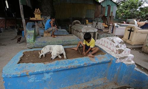 Một cậu bé chơi đùa trên ngôi mộ mà cậu gọi là nhà tại nghĩa trang Smor San. Ảnh: Khmer Times.