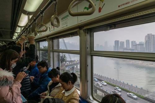 Những hành khách trên một chuyến tàu điện tại Trung Quốc. Mạng lưới xe công cộng phát triển, dịch vụ chia sẻ xe nở rộ khiến giới trẻ dần ít mua xe hơi. Ảnh: Gilles Sabrié