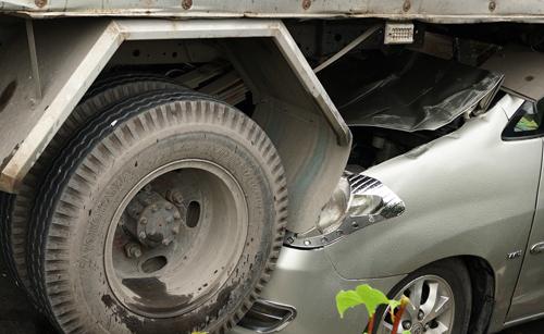 Đầu xe 7 chỗ bị biến dạng khi lao vào gầmxe tải. Ảnh: Minh Tân.