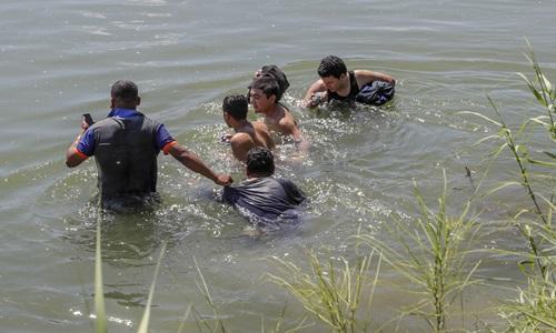 Một nhóm người di cư đang vượt qua sông Rio Grande ở biên giới Mỹ - Mexico tháng 12/2018. Ảnh: AP.