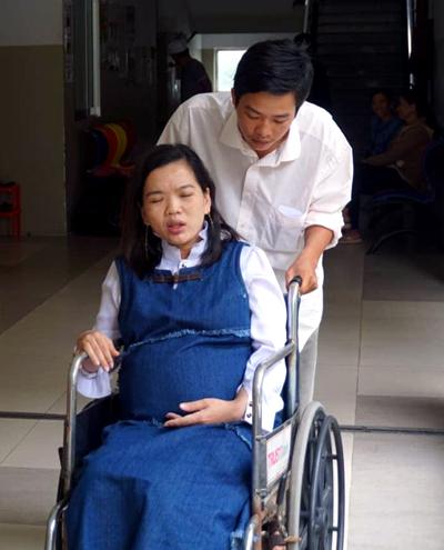 Chị Nhi được chồng đẩy trên xetạibệnh viện. Ảnh: Hằng My.