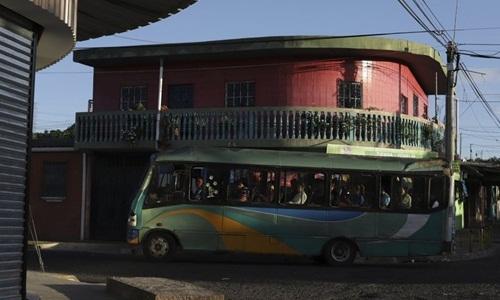 Chiếc xe buýt đi qua một con phố hẹp ở Altavista ngày 27/6. Ảnh: AP.