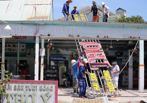 Công nhân tháo dỡ các hạng mục xây không phép tại nhà hàng hải sản Thơ Ý. Ảnh: Nguyễn Đông.