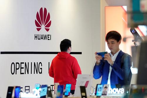Người dùng trải nghiệm điện thoại thông minh của Huawei tại trung tâm thương mại ở Thượng Hải hôm 16/5. Ảnh:Reuters.