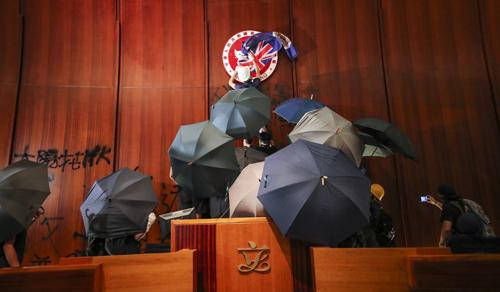 Người biểu tình phun khẩu hiệu phản đối chính quyền bên trong trụ sở Hội đồng Lập pháp tối 1/7. Ảnh: SCMP.