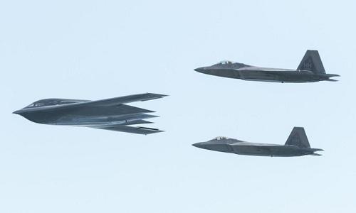 Hai tiêm kích F-22 hộ tống oanh tạc cơ B-2 bay qua Hawaii hồi tháng 1. Ảnh: USAF.
