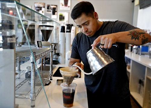 Quản lý Adam Alvarez đang pha chế cafe đen ở quán 7 Leaves,thành phố Garden Grove, quận Cam. Ảnh: LA Times