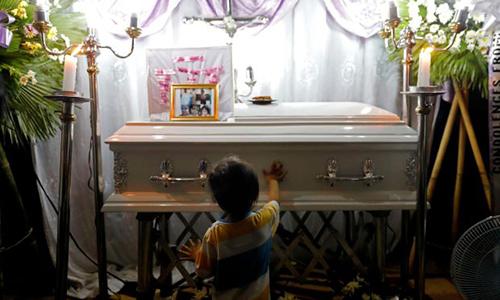 Anh trai của béMyca Ulpina đứng trước quan tài em tại Rodriguez, tỉnh Rizal, Philippines ngày 5/7. Ảnh:Reuters.