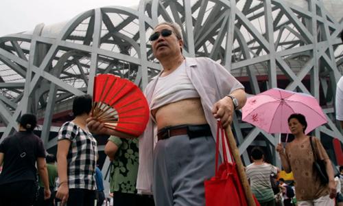 Một người đàn ông trung niên vén áo trước sân vận động Tổ Chim ở Bắc Kinh. Ảnh: AP.