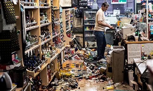 Nhân viên một cửa hàng bách hóaở trạm xăng dầu ở Ridgecrest hôm 6/7 giữa đống ngổn ngang sau trận động đất hôm trước. Ảnh: Guardian.