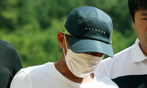 Nghi phạm đánh vợ Việt (giữa) bị áp giải ra tòa án thành phố Gwangju, tỉnh Jeollan Nam hôm 8/7. Ảnh: Yonhap