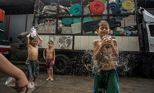 Trẻ em chơi đùa với các cốc và bình nhựa bên ngoài một cơ sở phân loại rác ở làngCanumay West Ảnh:Guardian