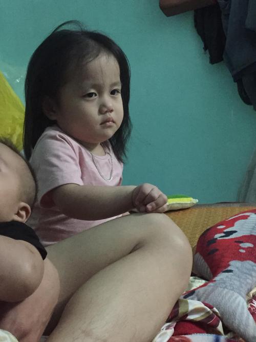 Cô bé giận ra mặt vì bố mải bế em.