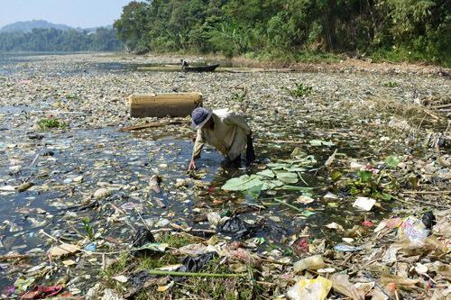 Một ngườithu gom rác thải nhựa để tái chế trên sông Citarum, Indonesia hôm 26/6. Ảnh: AFP.