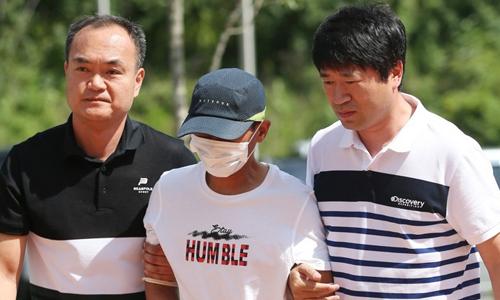 Người chồng Hàn Quốc, giữa, bị cảnh sát bắt sau khi hành hung vợ Việt hôm 4/7. Ảnh: Yonhap.