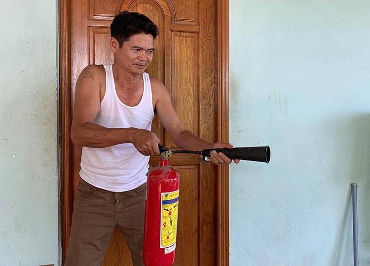 Ông Ngà và chiếc bình chữa cháy dùng chống trả nhóm tấn công. Ảnh: Minh Tâm.
