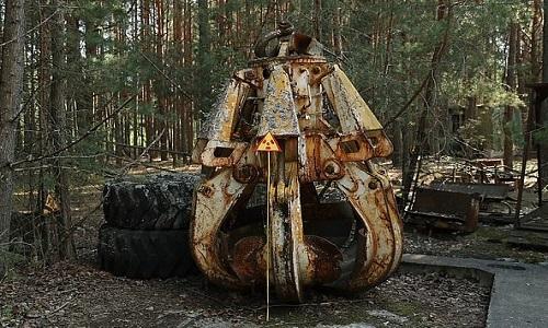 Chiếc móng vuốt máy xúc nhiễm phóng xạ bị bỏtrong rừng. Ảnh: AFP.