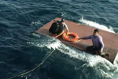 Các thuyền viên ngồi trên thùng dầu chờ cứu nạn. Ảnh: Đ.T