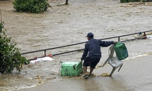 Người đàn ông cố gắng di chuyển trong nước lũ tại Kalanki, Nepal ngày 12/7. Ảnh: AFP.