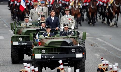 Tổng thống Pháp Emmanuel Macron (bên trái, xe đầu tiên) và Tham mưu trưởng Quân đội Pháp Francois Lecointre được chở tới tham dự buổi duyệt binh ngày 14/7. Ảnh: Reuters.