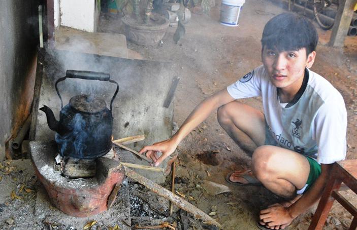 Tùng đun nước bằng bếp củi giúp mẹ. Ảnh: Phạm Linh.