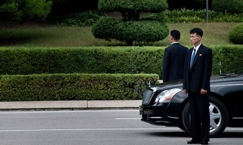 Hai vệ sĩ đứng gác bên cạnh một chiếc xe limousine của lãnh đạo Triều Tiên. Ảnh: AFP.