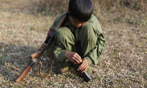 Một phiến quân 15 tuổi thuộc Quân đội Liên minh Dân chủ Quốc gia Mynamar gần căn cứ quân sự ở khu vực Kokang hôm 11/3/2015. Ảnh: Reuters.