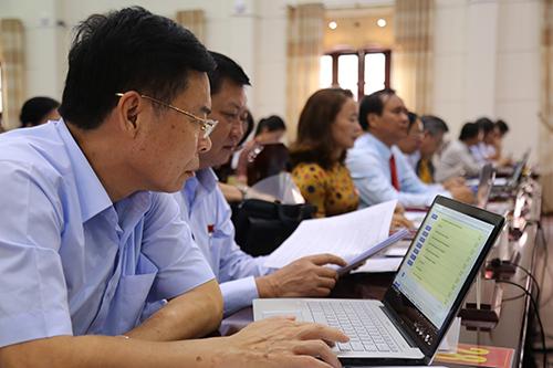 Các đại biểu HĐND Quảng Trị ứng dụng công nghệ thông tin để xử lý công việc. Ảnh: Hoàng Táo