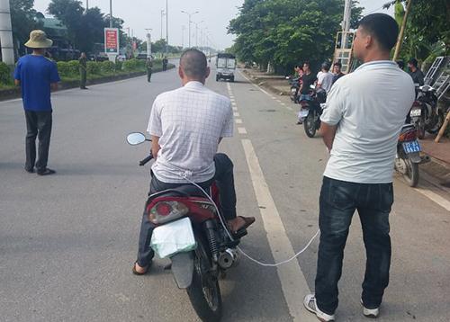 Toán thực nghiệm lại cảnh ngồi trên xe máy nhìn đồng bọn bắt cóc thiếu nữ giao gà. Ảnh: Thu Trang.