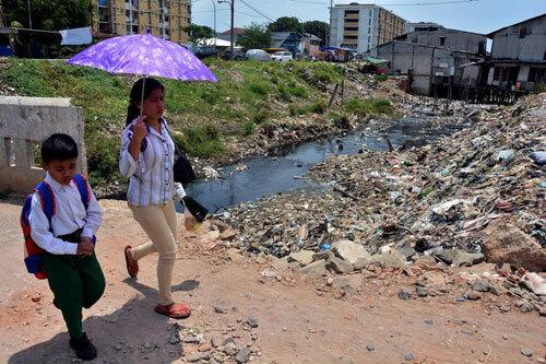 Người dân Jakarta đi qua một con mương ô nhiễm. Ảnh: Jakarta Post.