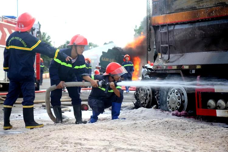 Cảnh sát chia hai tốpdập đám cháy xe bồn và liên tục phun nước dập lửa xe ben cháy âm ỉ.Ảnh: Nguyễn Khoa.