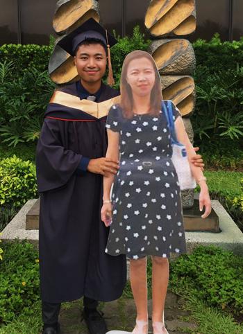Alinsog mặc trang phục cử nhân, chụp ảnh cùng bức hình cỡ người thật của người mẹ quá cố. Ảnh: Paulo John Alinsog.