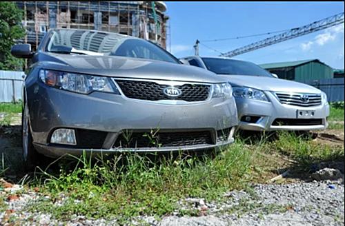 Một mẫu Kia nhập khẩu được đưa về Việt Nam để né Thông tư 20 hồi 2011. Vì không đủ không gian có mái che, xe buộc phải tận dụng một bãi đất trống mà chủ công ty thuê được, bất chấp nắng mưa. Ảnh: Hồng Anh - Nhật Minh