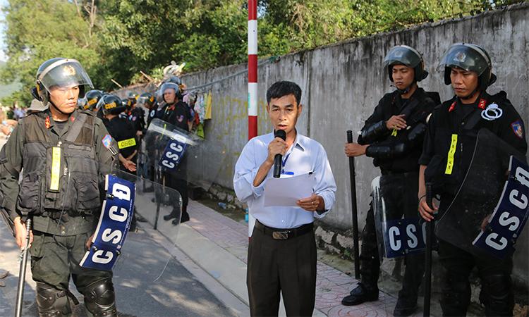 Ông Trần Đình Ơn, Chủ tịch UBND xã Châu Pha đọc quyết định cưỡng chế. Ảnh: Nguyễn Khoa.