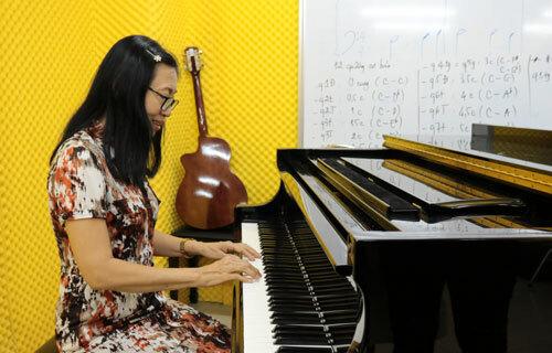 Bà Thư thử đàn Piano tại trường Đại học Văn Hiến. Ảnh: Lê Anh.