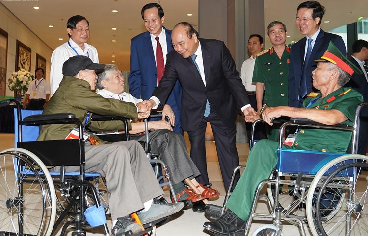 Thủ tướng thăm hỏi các đồng chí thương binh nặng tới dự buổi gặp mặt. Ảnh: VGP/Quang Hiếu