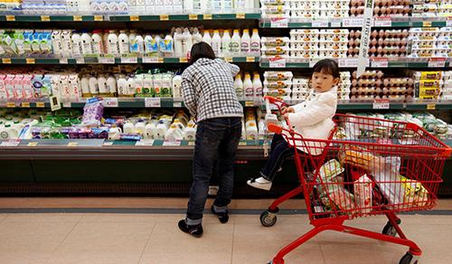 Một phụ nữ cùng con gái đi siêu thị ở Seoul. Ảnh: Reuters