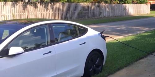 Chiếc Tesla Model 3 màu trắng đỗ trên vệ cỏ trước nhà người lạ, dây sạc cắm vào ổ điện trước sân.