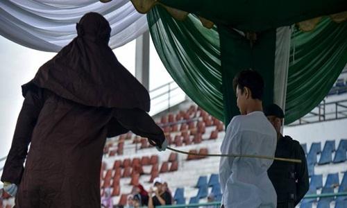 Người đàn ông bị đánh tại sân vận độngLhokseumawe, tỉnh Aceh, ngày 31/7. Ảnh:AFP.