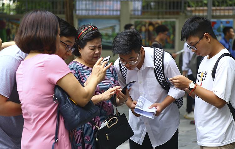Phụ huynh và thí sinh thảo luận tại điểm thi THCS Nghĩa Tân (Hà Nội) trong ngày làm thủ tục dự thi THPT quốc gia năm 2019. Ảnh: Dương Tâm